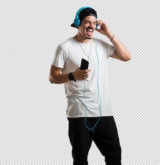 Homem jovem rapper feliz e divertido, ouvindo música, fones de ouvido modernos, sentindo o som e o ritmo felizes