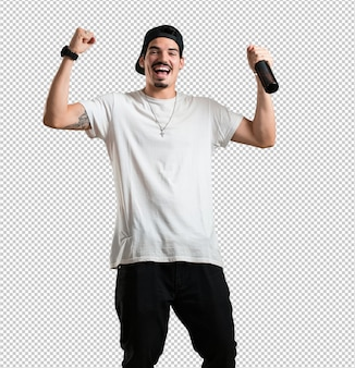 Homem jovem rapper feliz e divertido, segurando uma garrafa de cerveja, se sente bem após um dia intenso de trabalho.