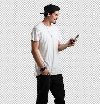 Homem jovem rapper feliz e relaxado, tocando o celular, usando a internet e redes sociais, sentimento positivo do futuro e modernidade