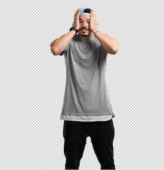 Homem jovem rapper frustrado e desesperado, irritado e triste com as mãos na cabeça