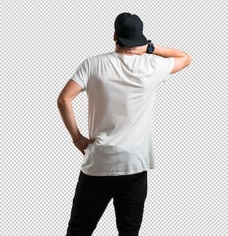 Homem jovem rapper mostrando para trás, posando e esperando, olhando para trás