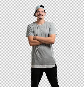 Homem jovem rapper olhando para cima, pensando em algo divertido e ter uma idéia, conceito de imaginação, feliz e animado