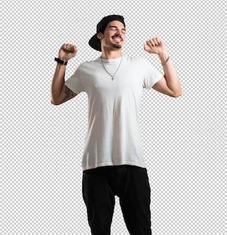 Homem jovem rapper ouvindo música, dançando e se divertindo, movendo-se, gritando e expressando felicidade, conceito de liberdade
