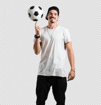 Homem jovem rapper sorrindo e feliz, segurando uma bola de futebol, atitude competitiva, animado para jogar um jogo