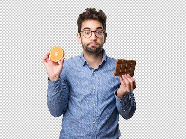 Homem jovem, segurando, um, laranja, e, um, barra chocolate