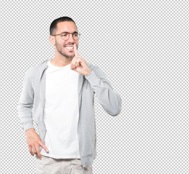 Homem jovem sério pedindo silêncio gesticulando com o dedo