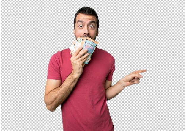Homem levando muito dinheiro apontando o dedo para o lado com um rosto surpreso