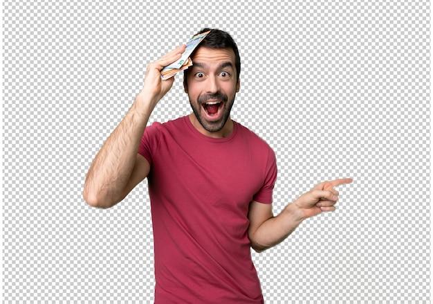 Homem levando muito dinheiro, apontando o dedo para o lado e apresentando um produto