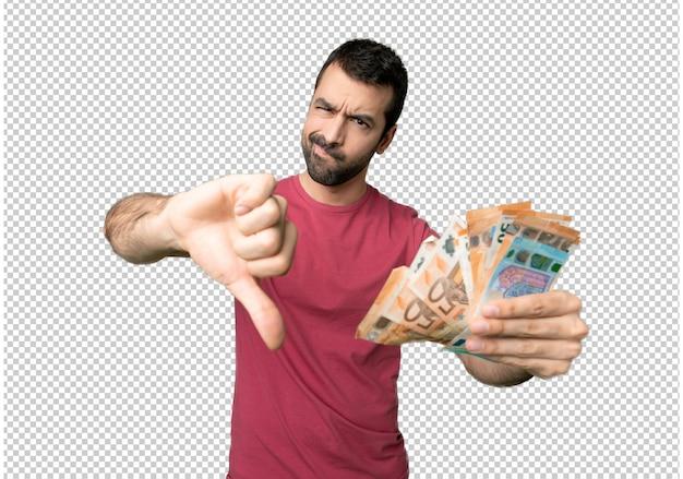 Homem levando muito dinheiro mostrando o polegar para baixo com as duas mãos