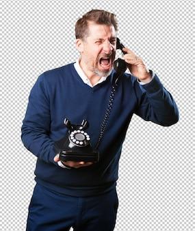 Homem maduro com raiva falando no telefone