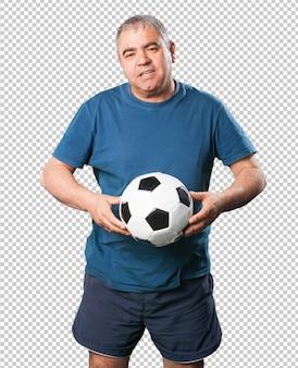 Homem maduro, jogando com bola de futebol