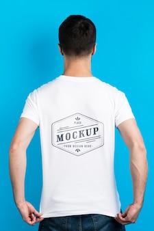 Homem mostrando a camisa do mock-up por trás