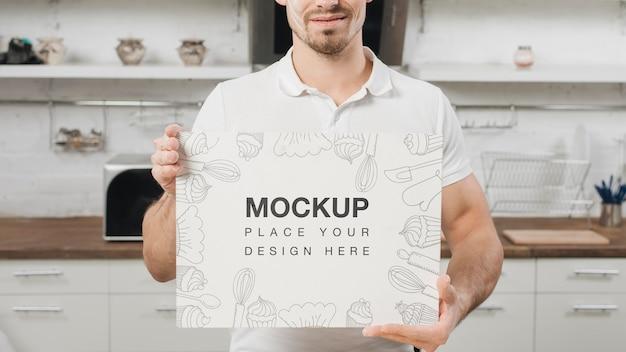 Homem na cozinha segurando um cartaz em branco