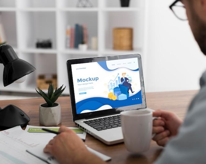 Homem na mesa com modelo de laptop