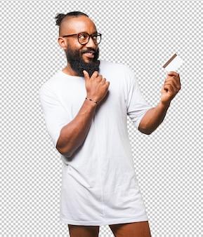 Homem negro a pensar com um cartão de crédito