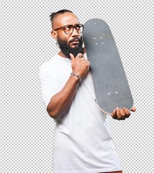 Homem negro a pensar com um skate