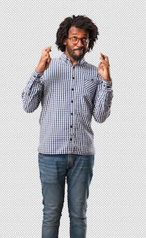 Homem negro bonito cruzando os dedos, deseja ter sorte para projetos futuros, animado, mas preocupado, expressão nervosa, fechando os olhos