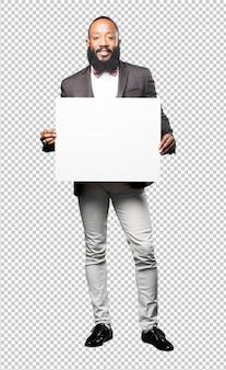 Homem negro de corpo inteiro segurando um cartaz