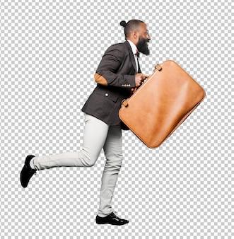 Homem negro de corpo inteiro segurando um saco de couro