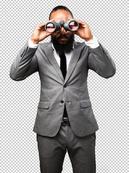 Homem negro de negócios segurando binóculos