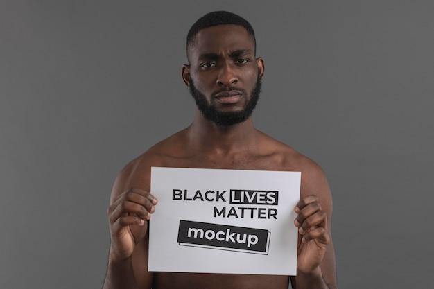 Homem negro de tiro médio segurando um pedaço de papel