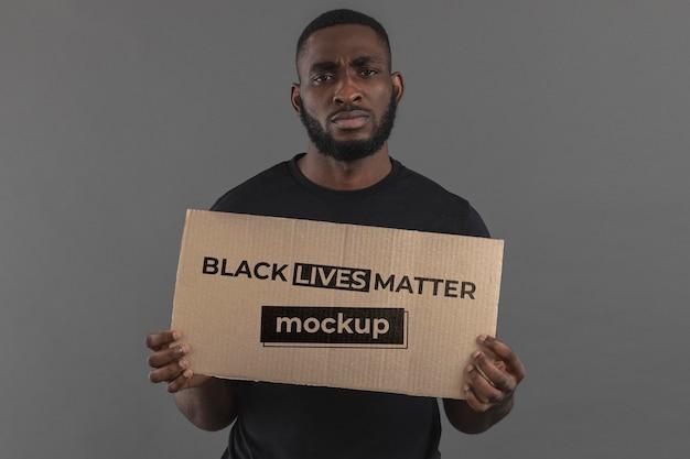 Homem negro de tiro médio segurando um pedaço de papelão