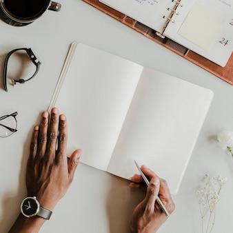 Homem negro escrevendo em uma maquete de caderno