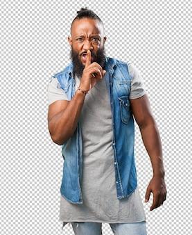 Homem negro, fazendo um sinal de silêncio