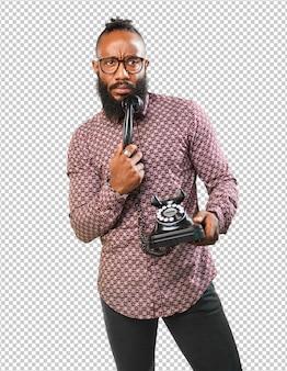 Homem negro, pensando, segurando telefone