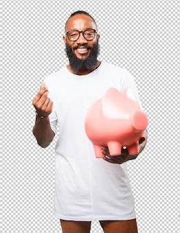 Homem negro segurando um cofrinho