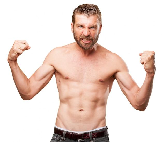 Homem novo que mostra seus músculos