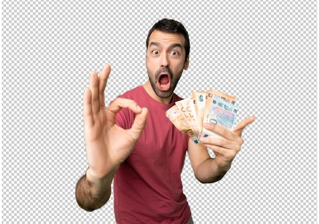 Homem que toma muito dinheiro que mostra o sinal aprovado com e que dá um polegar acima do gesto