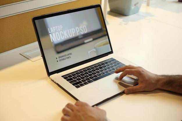 Homem que trabalha com o laptop no escritório local de trabalho maquete psd