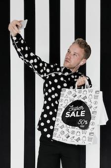 Homem satisfeito tomando selfie com sacolas de compras