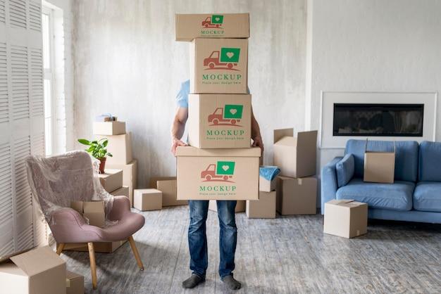Homem segurando caixas com objetos dentro de casa