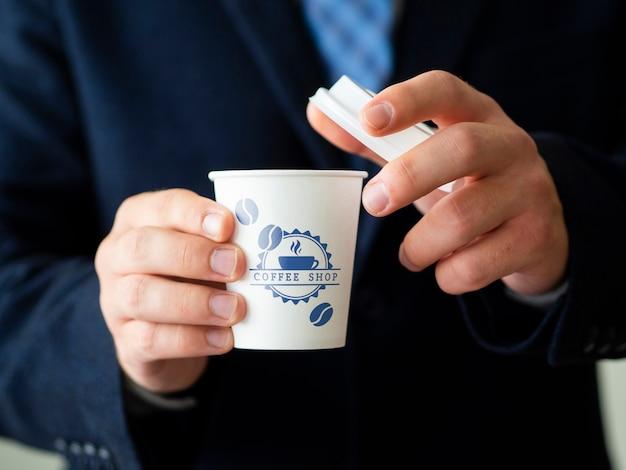 Homem segurando um modelo de xícara de chá