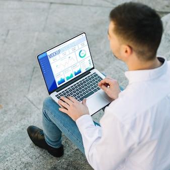 Homem segurando uma maquete de laptop ao ar livre