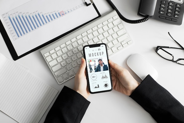 Homem segurando uma maquete de smartphone no escritório