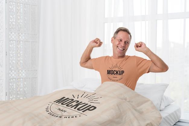Homem sênior na cama com tiro médio