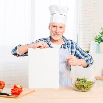 Homem sênior na cozinha segurando uma maquete de papel