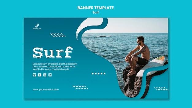 Homem sentado nas pedras ao lado de um banner de prancha de surf