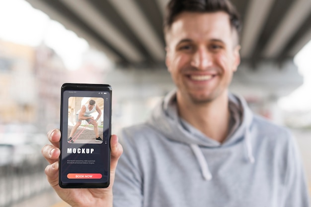 Homem sorridente segurando um smartphone enquanto faz exercícios ao ar livre