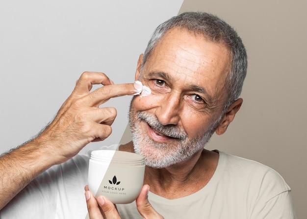 Homem sorridente sênior segurando um recipiente de creme