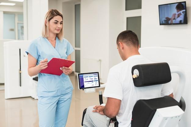Homem usando cadeira de reabilitação e enfermeira em pé ao lado dele