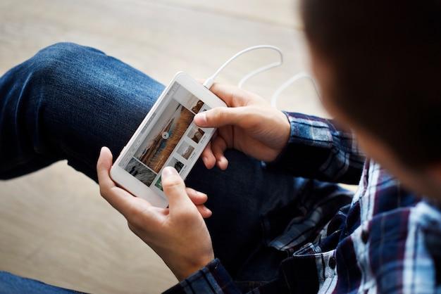 Homem usando um smartphone e playlist de música na tela