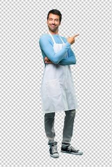 Homem vestindo um avental apontando para o lado com um dedo para apresentar um produto
