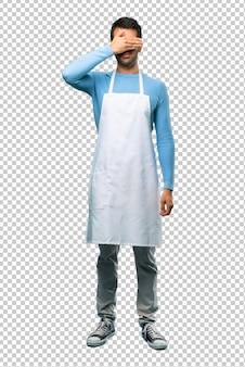 Homem vestindo um avental cobrindo os olhos pelas mãos. não quero ver algo