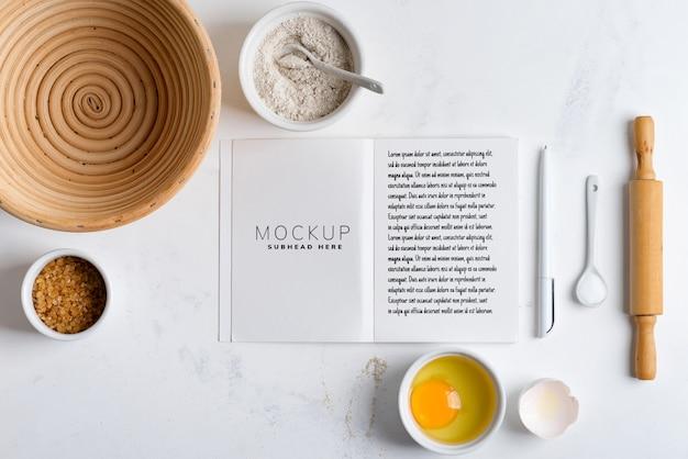 Ingredientes de cozimento com livro de receitas de maquete