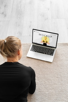 Instrutor de ioga olhando para uma maquete de laptop