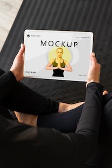 Instrutor de ioga segurando uma maquete de tablet